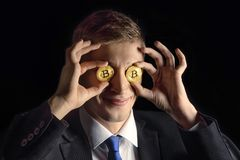 Happy young funny attractive businessman trader holding bitcoin cryptocurrency instead of eyes,  on black royalty free stock photo