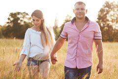 Happy young future parents have stroll across green meadow, hold hands, enjoy calm atmosphere, have happy expressions, anticipate. For baby. People, family stock photo