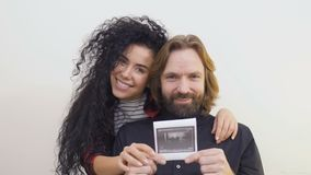 Happy young future parents with photo of ultrasound their future baby. Young married couple stands against white wall. The woman show a photo of ultrasound of stock video footage