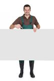 Happy young gardener presenting empty banner. Isolated on white Stock Photo