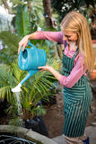 Happy young gardener watering plants at garden Royalty Free Stock Image