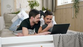 Happy young Gay couple of men are using modern laptop computer lying in bed in the bedroom. Cute male gay couple stock video footage