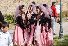 Happy young Georgian girls in vintage dresses with veils emotionaly talking during festival royalty free stock photos