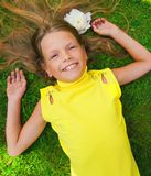 Happy young girl. Lying on a green grass Royalty Free Stock Image