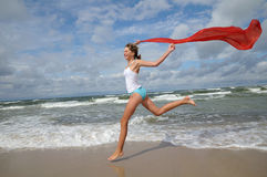 Happy young girl on the beach. Happy young girl with red scarf on the beach Stock Images