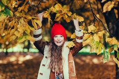 Happy young girl. In a beautiful autumn park under leaves Stock Photo