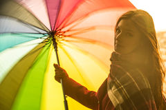 Happy young girl. Beautiful young and smiling red head girl twisting and spinning a rainbow colored umbrella during a sunset in front of the Italian city of Stock Photography