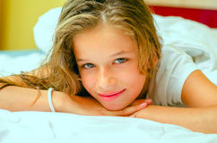 Happy young girl in bed Stock Photos
