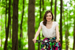 Happy young girl on bicycle in summer park Stock Photo