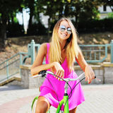 Happy young girl on a bicycle in summertime Royalty Free Stock Images