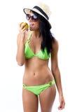Happy Young girl in bikini, eating an apple Stock Image