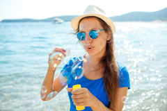 Happy young girl blowing soap bubbles on the seashore Royalty Free Stock Images