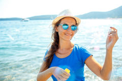 Happy young girl blowing soap bubbles on the seashore Stock Image