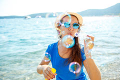 Happy young girl blowing soap bubbles on the seashore Royalty Free Stock Photo
