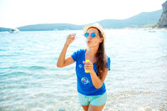 Happy young girl blowing soap bubbles on the seashore Royalty Free Stock Photos