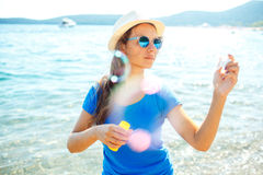 Happy young girl blowing soap bubbles on the seashore Stock Photos