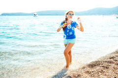Happy young girl blowing soap bubbles on the seashore Stock Images