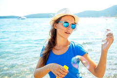 Happy young girl blowing soap bubbles on the seashore Stock Photography