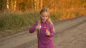 Happy young girl blowing soap-bubbles, twisting and turning around. Outdoor autumn. Slow motion. Happy young girl blowing soap-bubbles, twisting and turning stock video