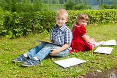 Happy Young  girl  and  boy Writing  .Smiling in. Happy Young girl and boy Writing letter  . Smiling in summer Garden Stock Image