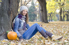 Happy young girl with braces smiling, sitting on the ground in park. Happy young girl with braces smiling, healthy lifestyle, sitting next to a pumpkin Royalty Free Stock Photography