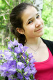 Happy young girl with brigth bluebell flowers Royalty Free Stock Image