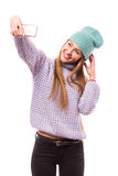 Happy young girl with cap on the head taking selfie from phone (photo of herself)  on white background Royalty Free Stock Photos