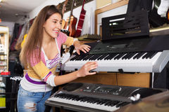 Happy young girl choosing synthesizer Royalty Free Stock Image