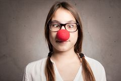 Happy young girl with a clown nose Stock Image
