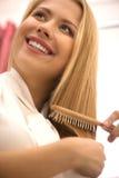 Happy young girl combing hair. Stock Photos