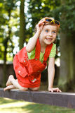Happy young girl crawl on the beam in the park Stock Photography