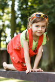 Happy young girl crawl on the beam in the park Stock Photos