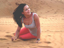 Happy young girl in the desert. Beautiful girl wearing in pink trousers and grey shirt siting on the sands in the desert of Dubai. the wind blowing her hair in a stock images