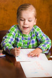 Happy young girl drawing a picture for mommy. Royalty Free Stock Photos