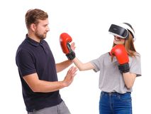 A girl in boxing gloves and virtual reality glasses beats beside a standing guy. Isolated on white. stock images