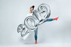 Happy young girl dressed in white t-shirt, jeans and pink socks holding balloons in the shape of numbers 2019 on the royalty free stock images