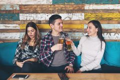 Happy young girl drinking beer with young man and socialise ignoring jealous sad woman royalty free stock photos