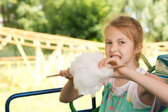 Happy young girl eating candy floss at the fair Royalty Free Stock Photos