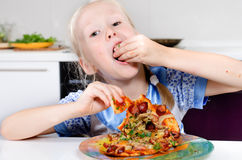 Happy young girl eating pizza Stock Images