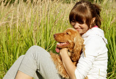 Happy young girl embracing her dog on the green gr Stock Photography