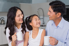 Happy young girl enjoying breakfast with parents Royalty Free Stock Photo