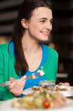 Happy young girl enjoying her dinner Royalty Free Stock Photo