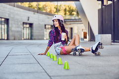 Happy young girl enjoying roller skating with coffee Royalty Free Stock Image
