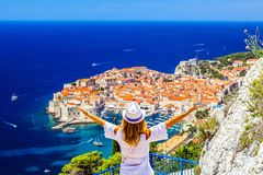 Summer holiday in Croatia- beautiful young female looks at old cityDubrovnik from aerial view. royalty free stock photos