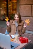 A happy girl sits in a cafe, is holding two autumn leaves and looking at an laptop. stock images