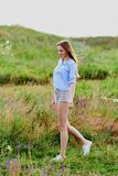 Happy young girl in the field. Happy smiling young girl in blue shirt and shorts in the field stock image