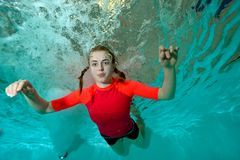 Happy young girl floats underwater with his arms outstretched to the sides on a blue background, in a red bathing suit. And looks at me. Bottom view from under Royalty Free Stock Image