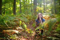 Happy young girl in forest on a fall day Stock Photo