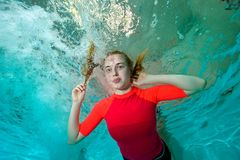 Happy young girl goes in for sports, swimming underwater on a blue background in a red swimsuit and looks at me. Bottom view from under the water. Portrait Royalty Free Stock Image