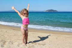 Happy young girl with hands up. On the beach Stock Photography